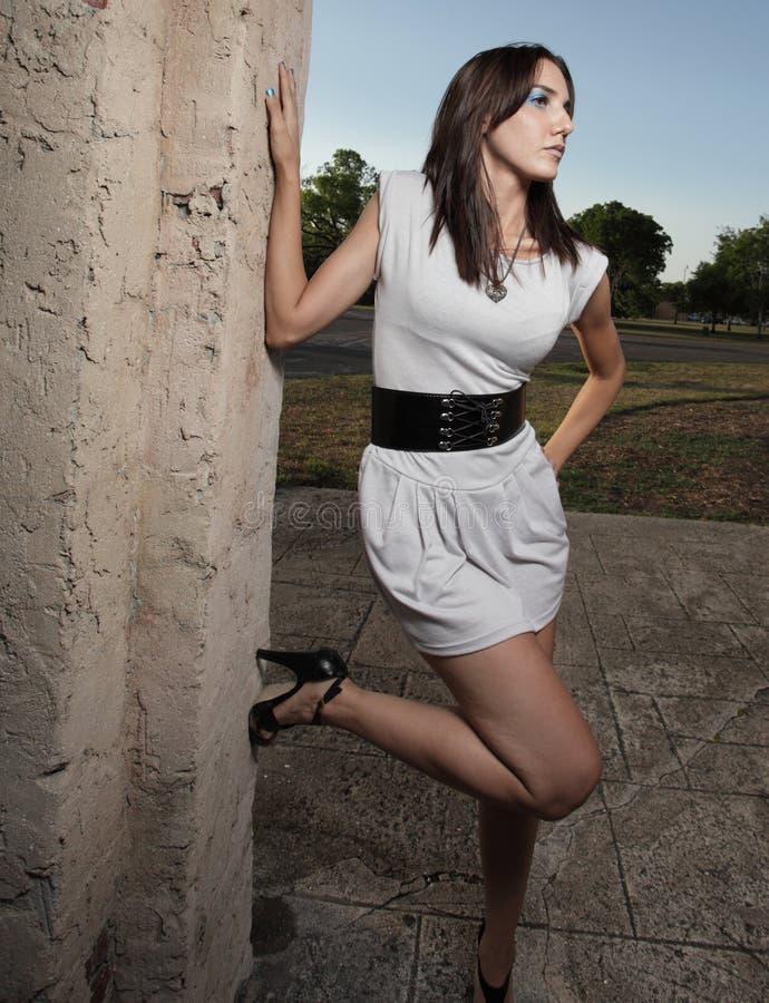 Reizvolle Frau, die auf einer Wand sich lehnt stockfotografie