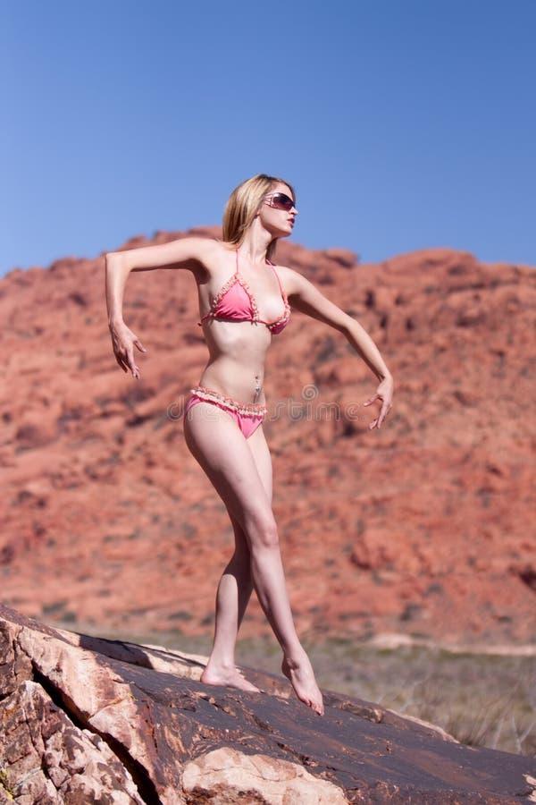 Reizvolle Frau, die auf roten Felsen aufwirft lizenzfreie stockbilder