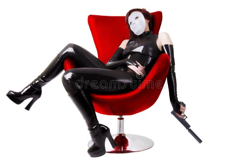 Reizvolle Frau, die auf Stuhl sitzt stockfotografie
