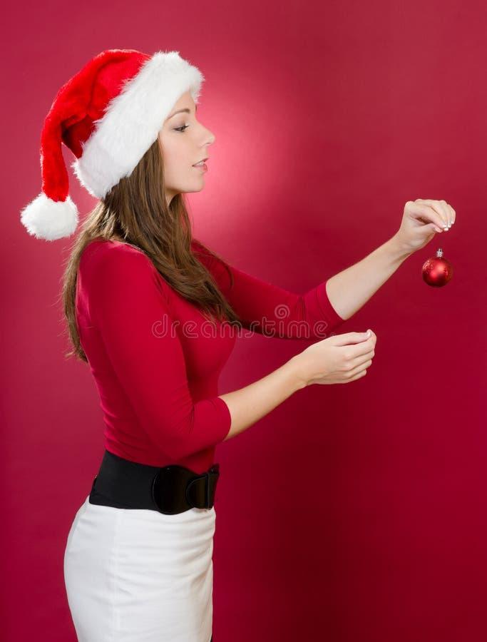 Reizvolle Frau, die eine Weihnachtskugel hängt stockfotos