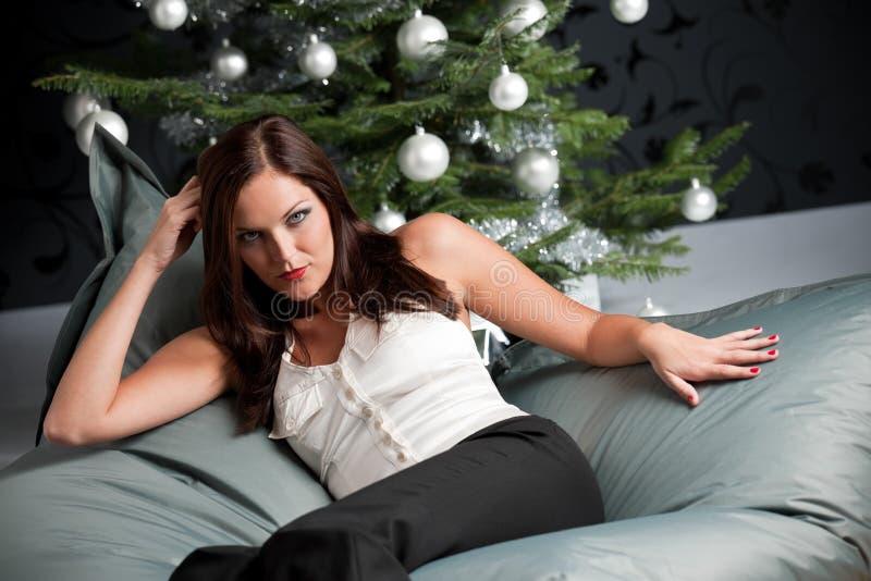 Reizvolle Frau, die vor Weihnachtsbaum aufwirft lizenzfreie stockfotos