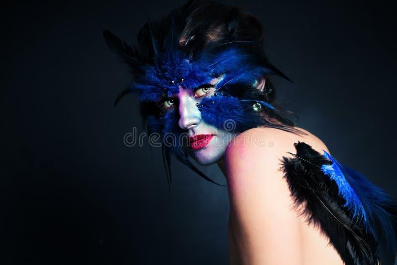 Reizvolle Frau - Hexe mit dem langen schwarzen Haar und Kürbislächeln und -blick zum Schuß Fantasie-Vogel-Frau mit künstlerischem lizenzfreie stockfotos