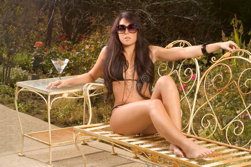 Reizvolle Frau im schwarzen Badeanzug ein Sonnenbad nehmend auf Bank stockbild