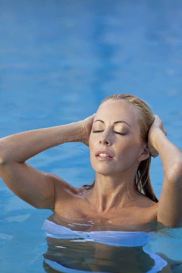 Reizvolle Frau im weißen Bikini im Swimmingpool lizenzfreie stockbilder