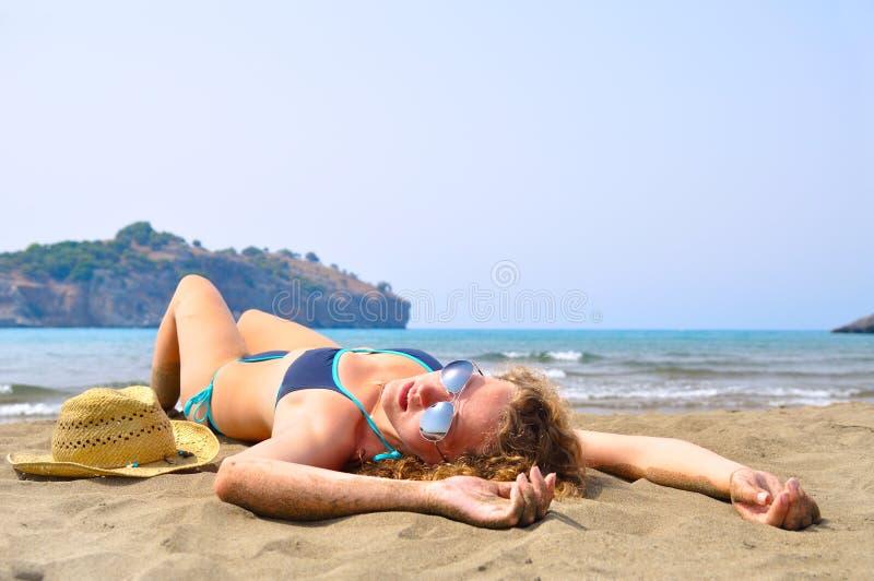 Reizvolle Frau liegt auf dem Strand stockfotografie