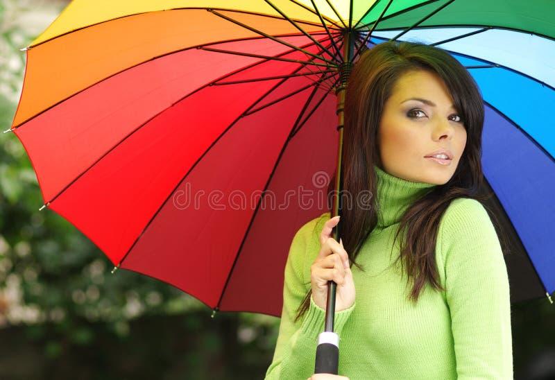 Reizvolle Frau mit buntem Regenschirm lizenzfreie stockfotos