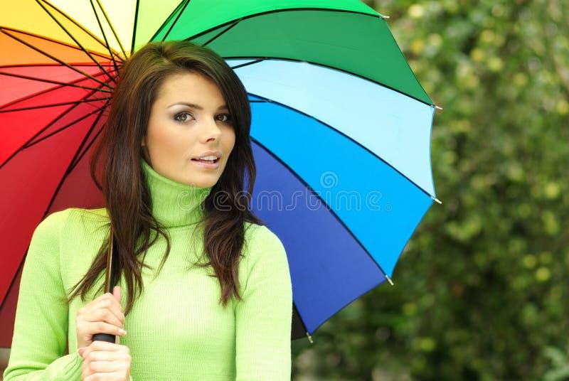 Reizvolle Frau mit buntem Regenschirm lizenzfreies stockbild
