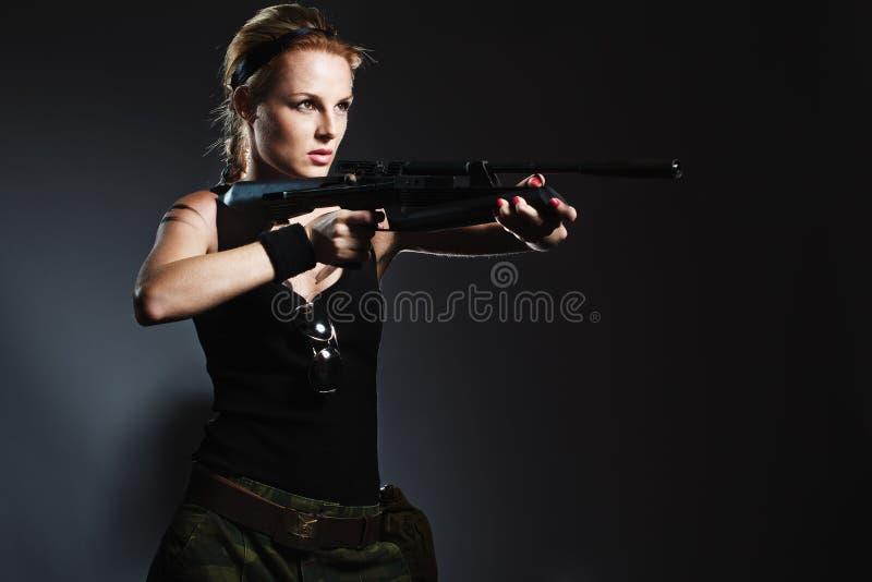 Reizvolle Frau mit Gewehr stockfoto