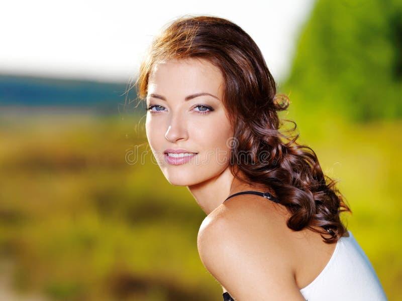 Reizvolle Frau mit schönem Gesicht draußen stockbild