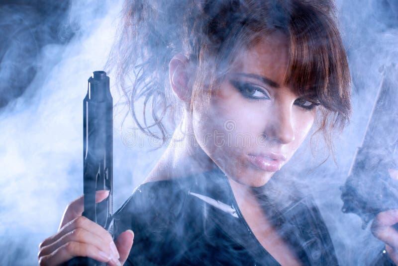 Reizvolle Frauenholdinggewehr mit Rauche stockbilder