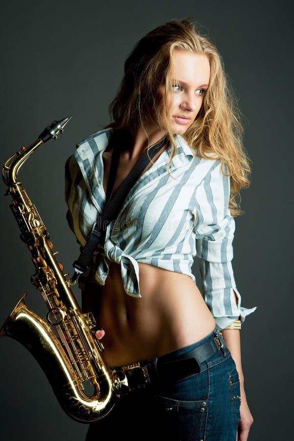 Reizvolle herrliche der Junge Blondine recht mit Saxophon stockfotos