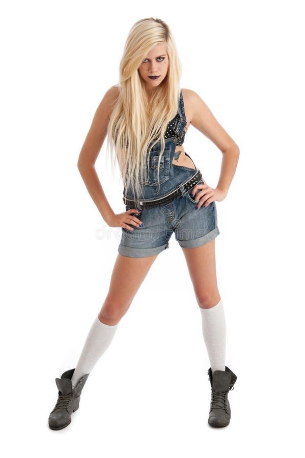Reizvolle junge blonde Frau in den Dungarees lizenzfreies stockbild