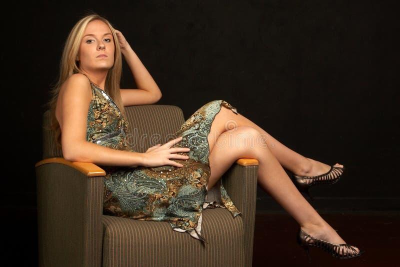 Reizvolle junge Blondine mit den Fahrwerkbeinen über Stuhl lizenzfreie stockfotografie