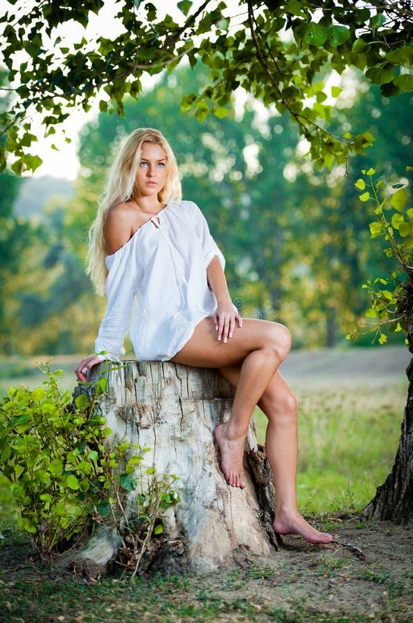 Reizvolle Junge Frau, Die Auf Stumpf Im Wald Sitzt