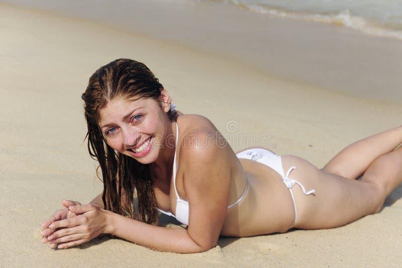 Reizvolle junge Frau, die im Sand auf dem Strand liegt stockbilder