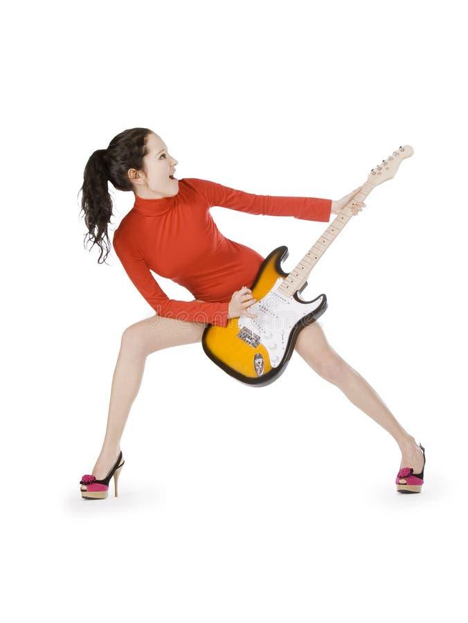 Reizvolle junge Frau, die mit Gitarre aufwirft stockbild