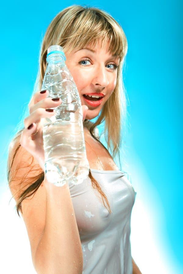 Reizvolle junge Frau mit Flasche im nassen T-Shirt stockfoto