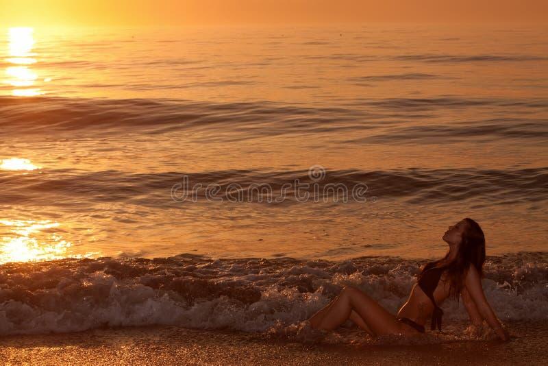 Reizvolle junge Frau am Strand während des Sonnenuntergangs lizenzfreie stockbilder