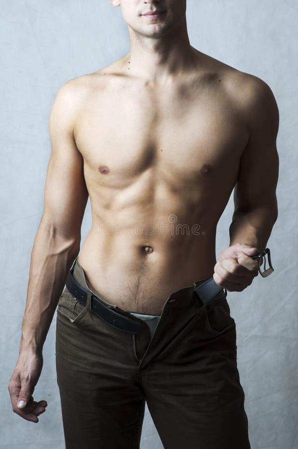 Reizvolle Karosserie des muskulösen jungen Mannes lizenzfreies stockbild