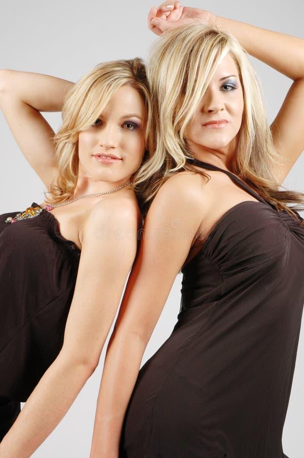 Reizvolle Mädchen, die zusammen aufwerfen lizenzfreie stockfotos