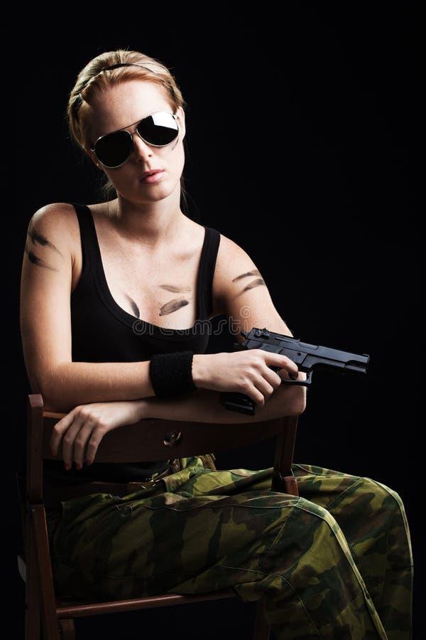 Reizvolle Militärfrau, die mit Gewehr aufwirft lizenzfreies stockfoto