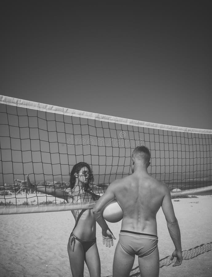 Reizvolle Paare Junge sportliche aktive Paare stehen nahes Volleyballnetz, Spielspiel am Sommertag Paare haben das Spaßspielen lizenzfreie stockfotos