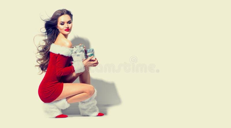 Reizvolle Sankt Weihnachtsschönheitsmädchen, welches das rote Kleid hält Geschenke trägt lizenzfreie stockfotografie