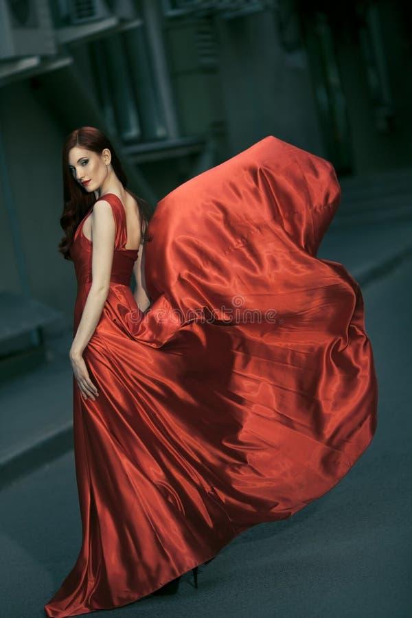 Reizvolle Schönheitsfrau in flatterndem rotem Kleid stockfotos