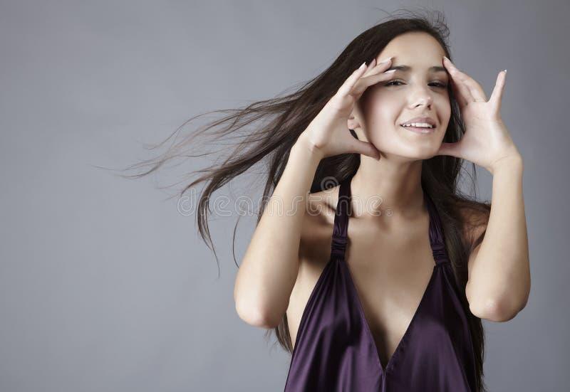 Reizvoller Brunette, der im silk violetten Kleid aufwirft stockbild