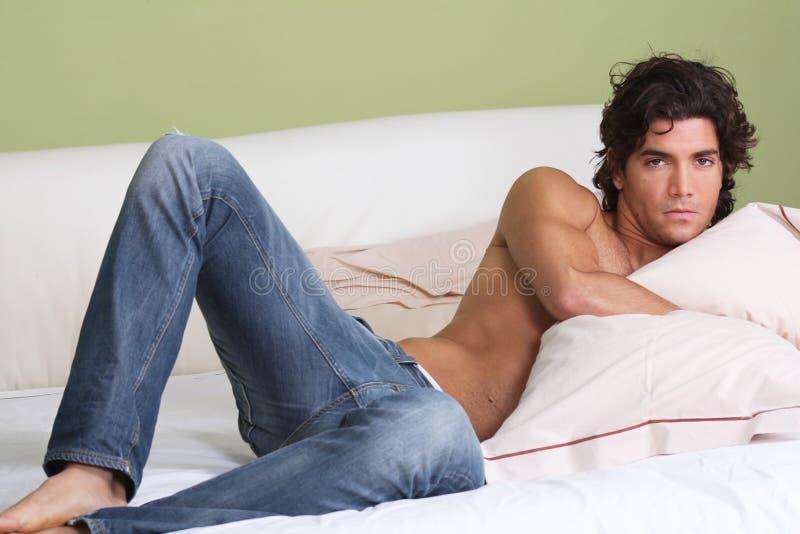 Reizvoller Mann, der im Bett mit nacktem Oberkörper liegt lizenzfreie stockfotografie