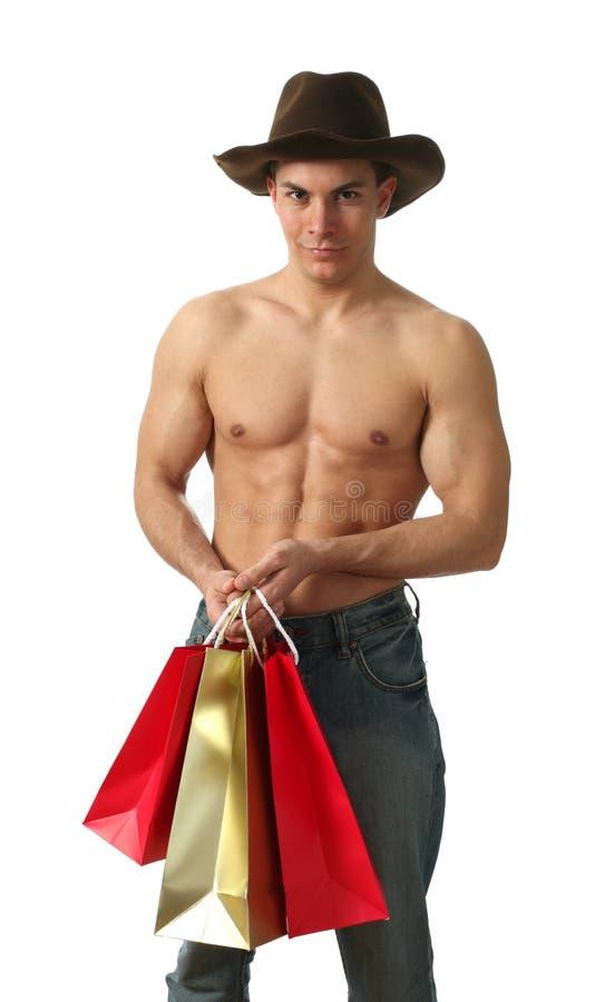Reizvoller Mann mit Einkaufen-Beuteln stockfoto