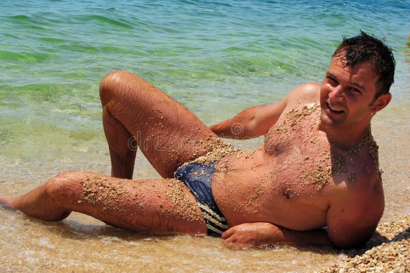 Reizvoller Mann am Strand stockfoto