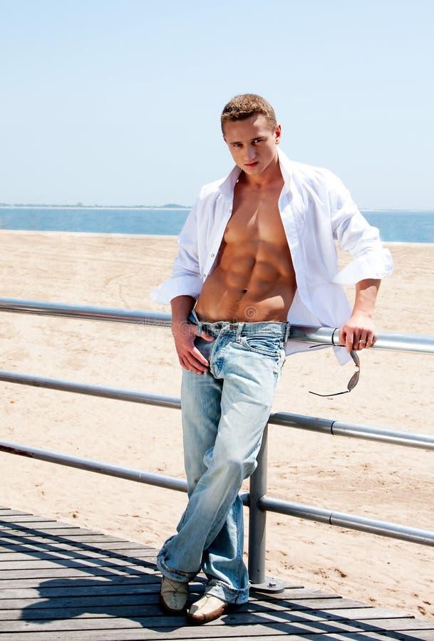 Reizvoller Mann am Strand stockbilder