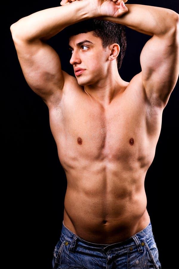 Reizvoller muskulöser Mann mit Pass-Sitzkarosserie lizenzfreie stockfotografie
