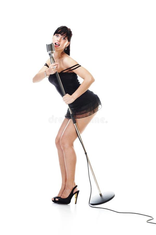 Reizvoller weiblicher Sänger, der das schwarze Kleid anhält ein r trägt lizenzfreie stockbilder