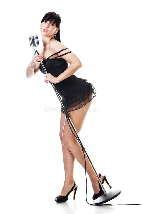 Reizvoller weiblicher Sänger, der das schwarze Kleid anhält ein r trägt stockfoto