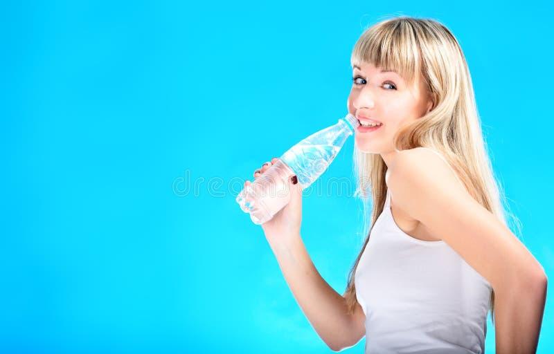 Reizvolles blondes Getränkwasser von der Flasche stockbilder