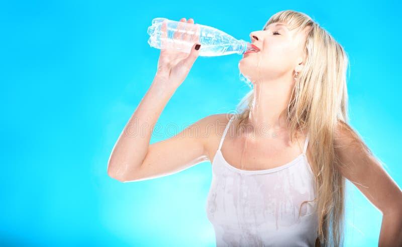 Reizvolles blondes Getränkwasser von der Flasche stockfoto