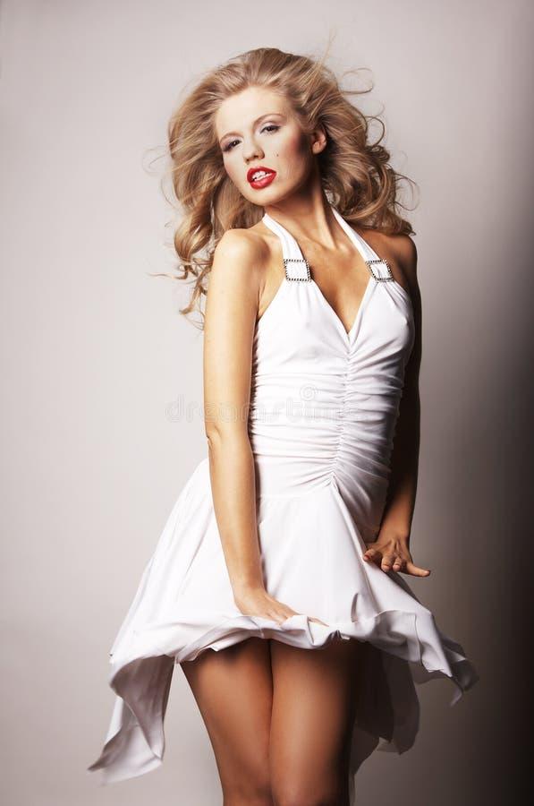 Reizvolles blondes Mädchen auf grauem Hintergrund stockfotografie