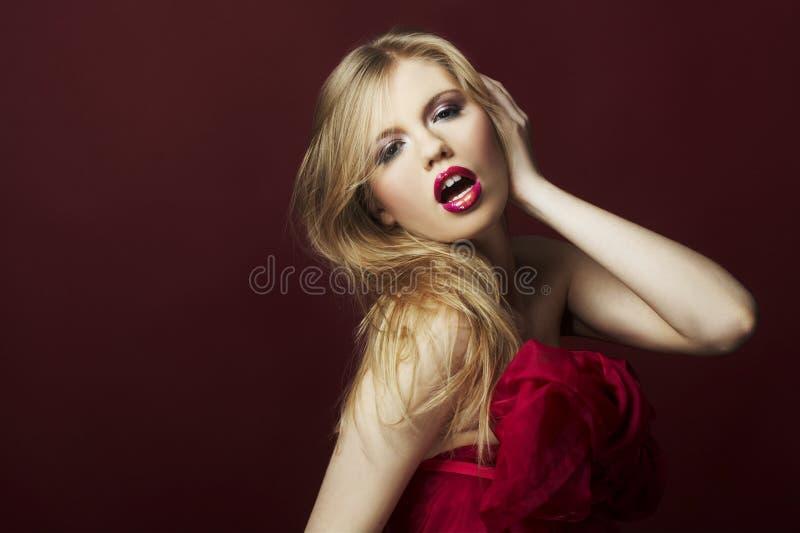 Reizvolles blondes Mädchen auf rotem Hintergrund lizenzfreie stockfotografie