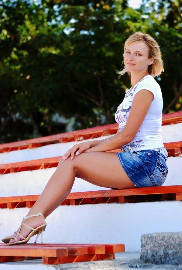Reizvolles blondes Mädchen, das in einem kurzen Jeansrock aufwirft lizenzfreies stockbild