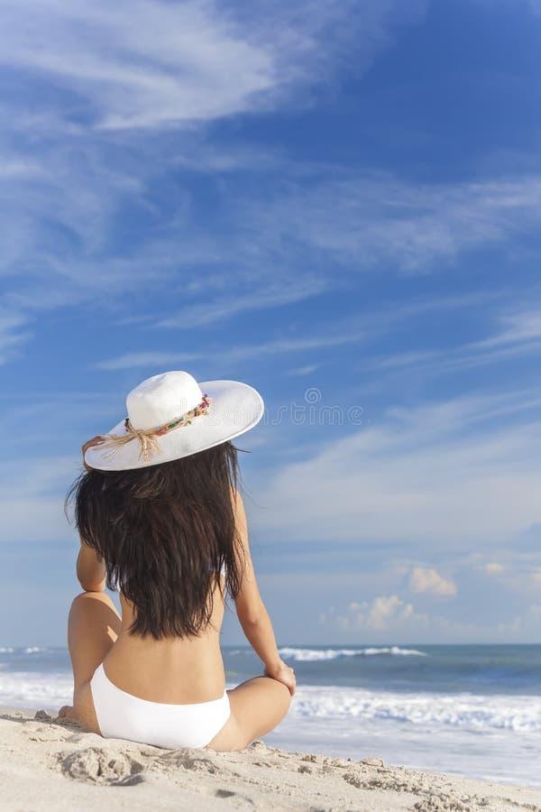 Reizvolles Frauen-Mädchen, das Sun-Hut u. Bikini auf Strand sitzt lizenzfreie stockfotografie