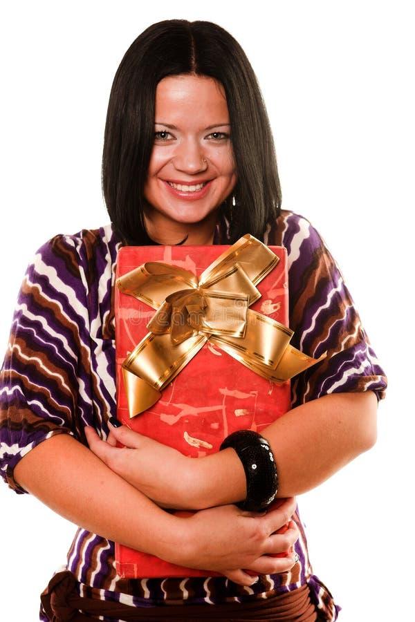 Reizvolles lächelndes Mädchen, das ein Geschenk anhält lizenzfreie stockbilder