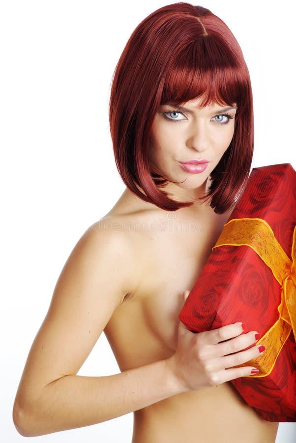 Reizvolles Mädchen, das ein Geschenk in der Verpackung anhält lizenzfreie stockbilder