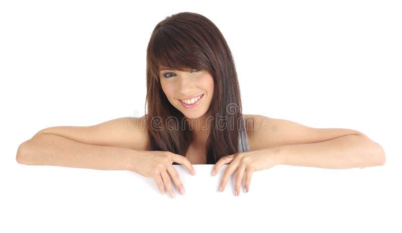 Reizvolles Mädchen, das einen unbelegten Vorstand anhält. stockbilder