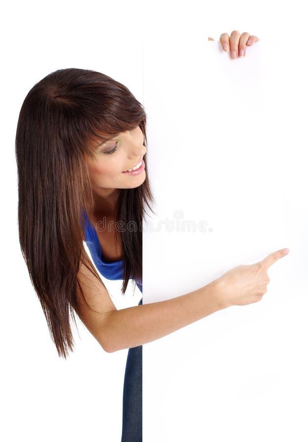 Reizvolles Mädchen, das leeren weißen Vorstand anhält stockbild
