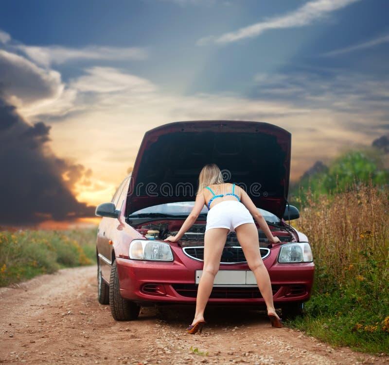 Reizvolles Mädchen, das unter der Autohaube schaut stockfoto