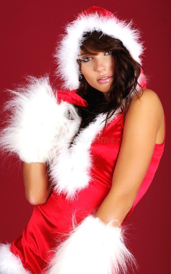 Reizvolles Mädchen, das Weihnachtsmann-Kleidung trägt lizenzfreies stockfoto