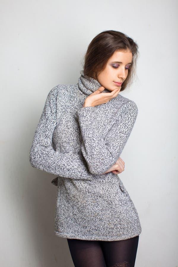 Reizvolles Mädchen in einer grauen Kleidung lizenzfreie stockbilder