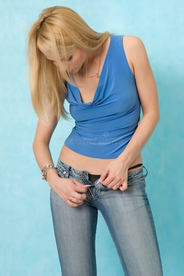 Reizvolles Mädchen knöpft Jeans auf. lizenzfreie stockfotografie